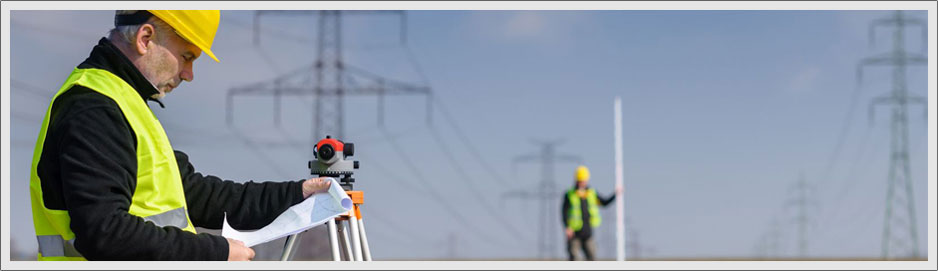 Two men surveying next to power lines